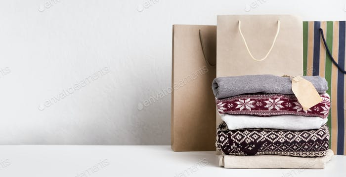 Warm sweaters with patterns and tag for text laying on white