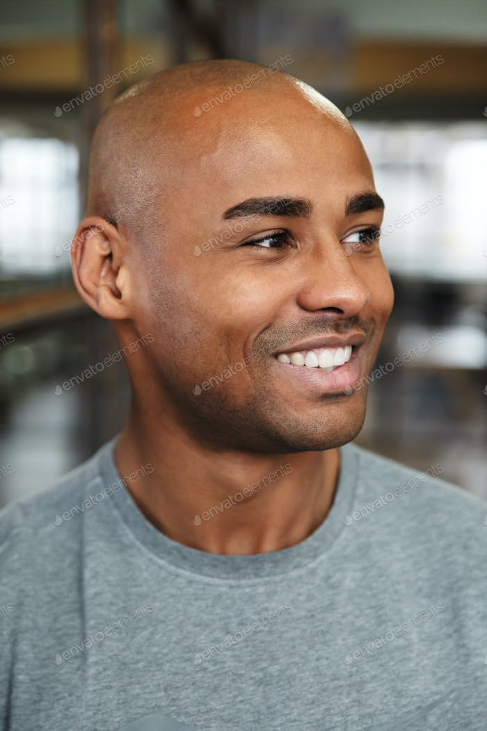 Image of bald african american man smiling and looking aside indoors