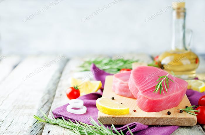 Tuna steak raw with lemon, rosemary, tomatoes and pepper