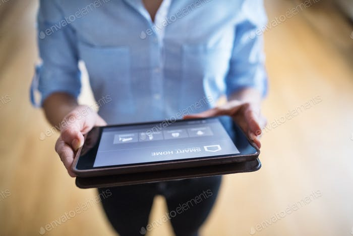 A woman holding a tablet with smart home screen.