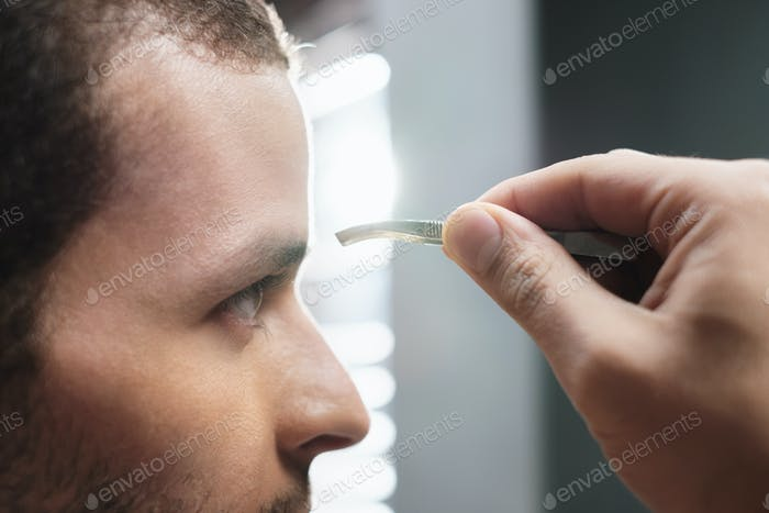 Closeup Of Male Face Man Plucking Eyebrow Hair For Beauty