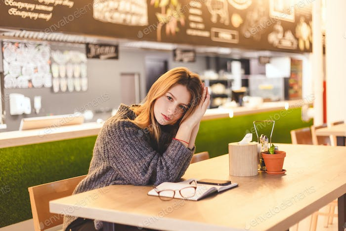 Young woman freelancer sitting in cafe after hard work day