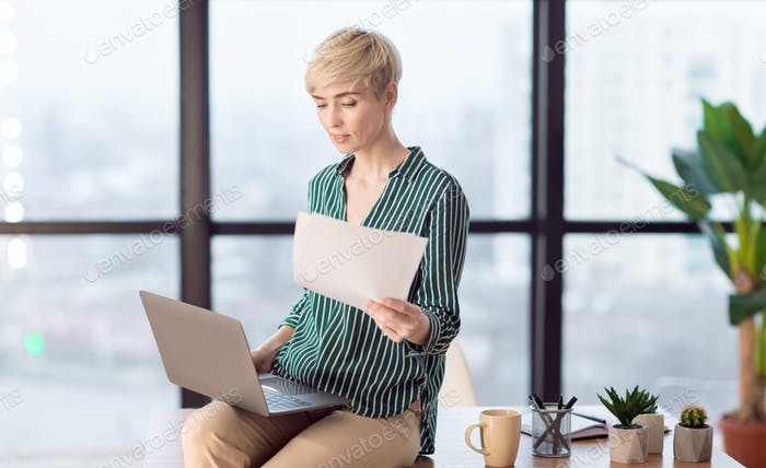 Businesswoman Working With Papers Sitting On Desk In Office