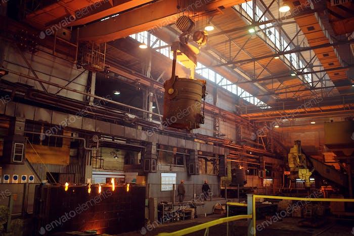 Crane with bucket of liquid metal on steel factory