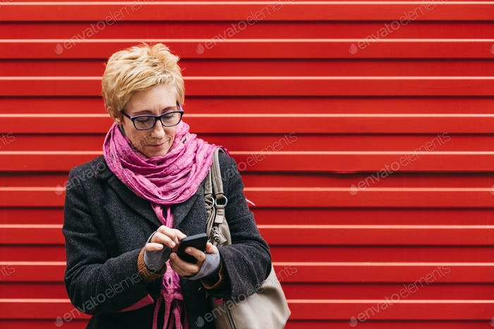 Erwachsene Frau mit Smartphone auf der Straße