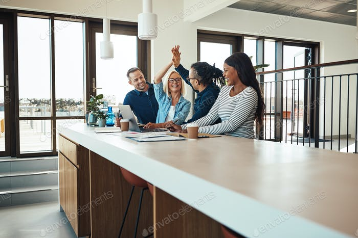 Smiling coworkers high fiving together during an office meeting