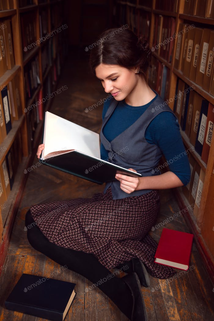 Student girl with open book in university library.