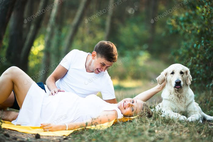 pregnant woman with husband lying in the park