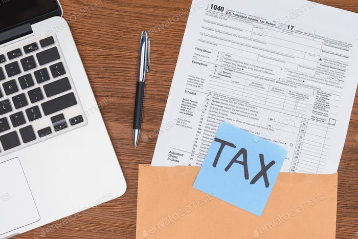 top view of tax form, laptop and blue card with 'tax' word at workplace