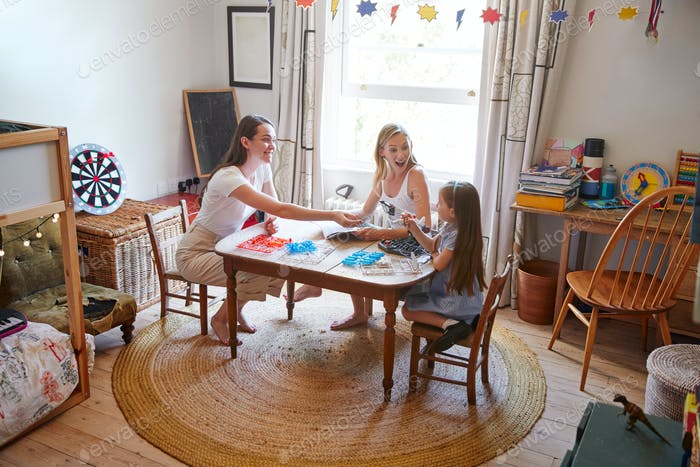 Same Sex Female Couple Making Robot From Kit With Daughter In Bedroom At Home Together