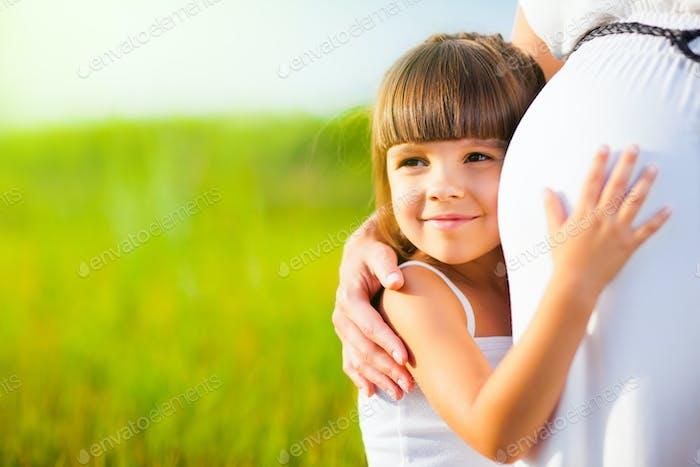 kleine Mädchen umarmt Mama schwanger Bauch