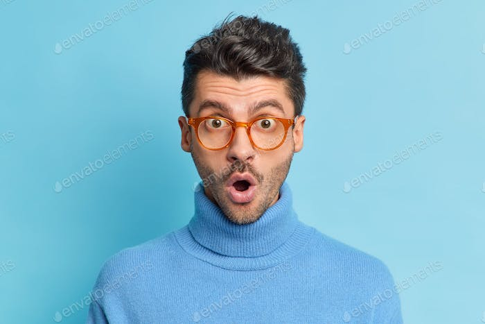 Close up portrait of shocked unshaven Caucasian man keeps mouth opened reacts on something breathtak