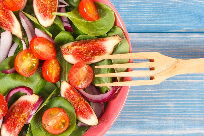 Fresh prepared fruit and vegetable salad with wooden fork, healthy nutrition concept