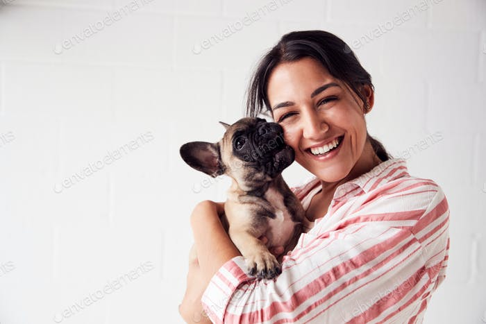 Studio Portrait Of Smiling Young Woman Holding Affectionate Pet French Bulldog Puppy