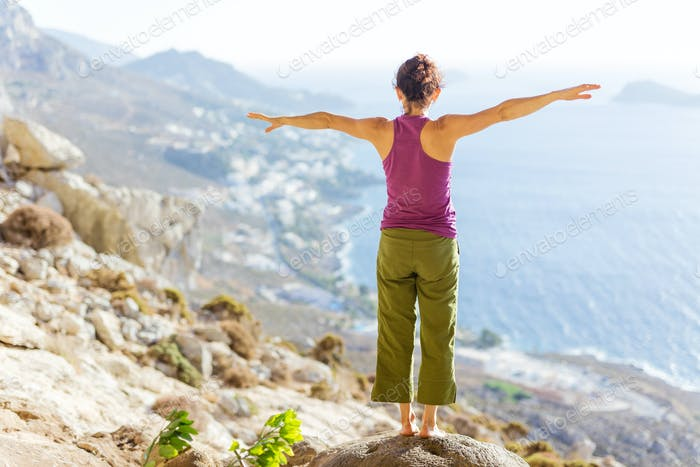Young Caucasian woman practicing yoga while standing on cliff