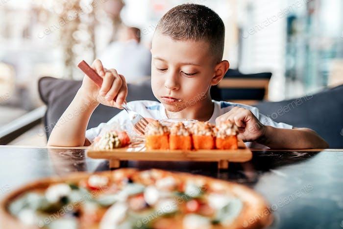 Junge genießt es, Sushi-Rollen im Outdoor-Café zu essen