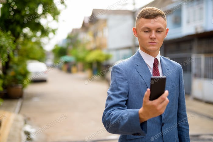 Young businessman using mobile phone in the streets outdoors