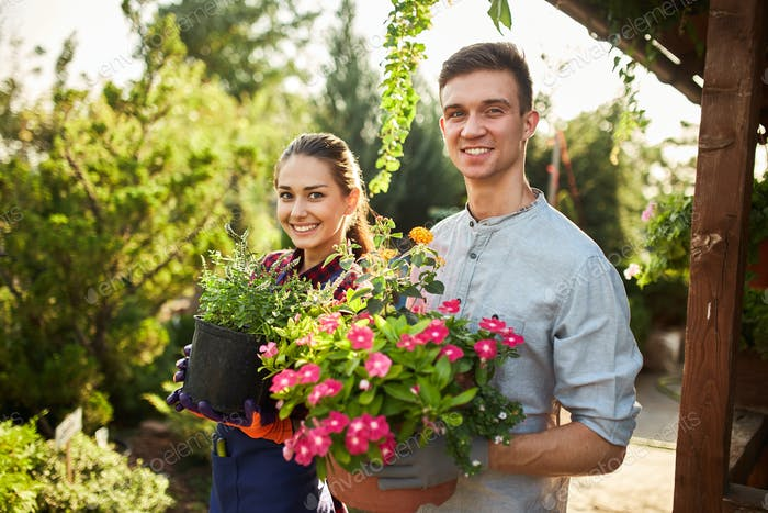 Gardeners happy boy and girl hold pots with plants in beautiful gardens on a warm sunny day
