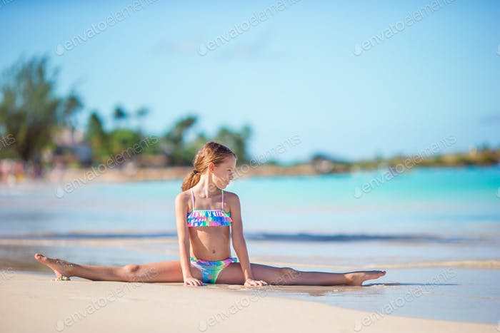 Adorable little girl sitting on white snow sand