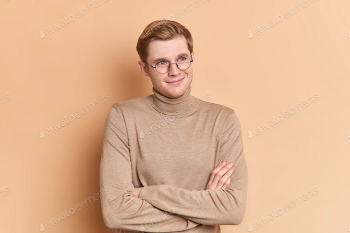 Dreamy satisfied blue eyed handsome male youngster stands crossed hands indoor looks into distance t