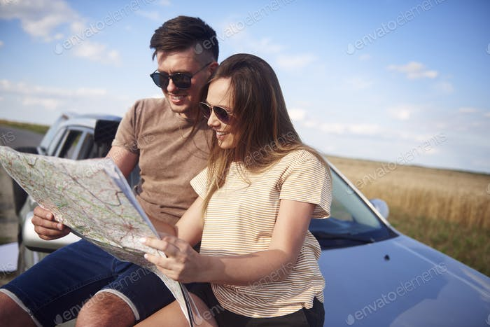 Couple with map choosing the best road for road trip