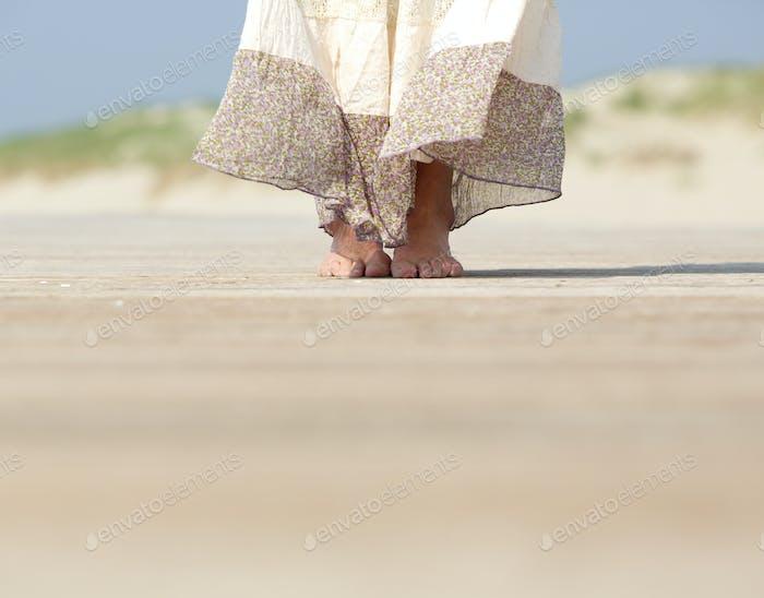 Female feet standing at the beach