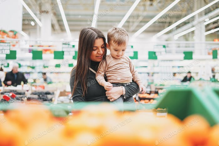Young woman mother with cute baby boy toddler child on hands buy fresh fruits in supermarket