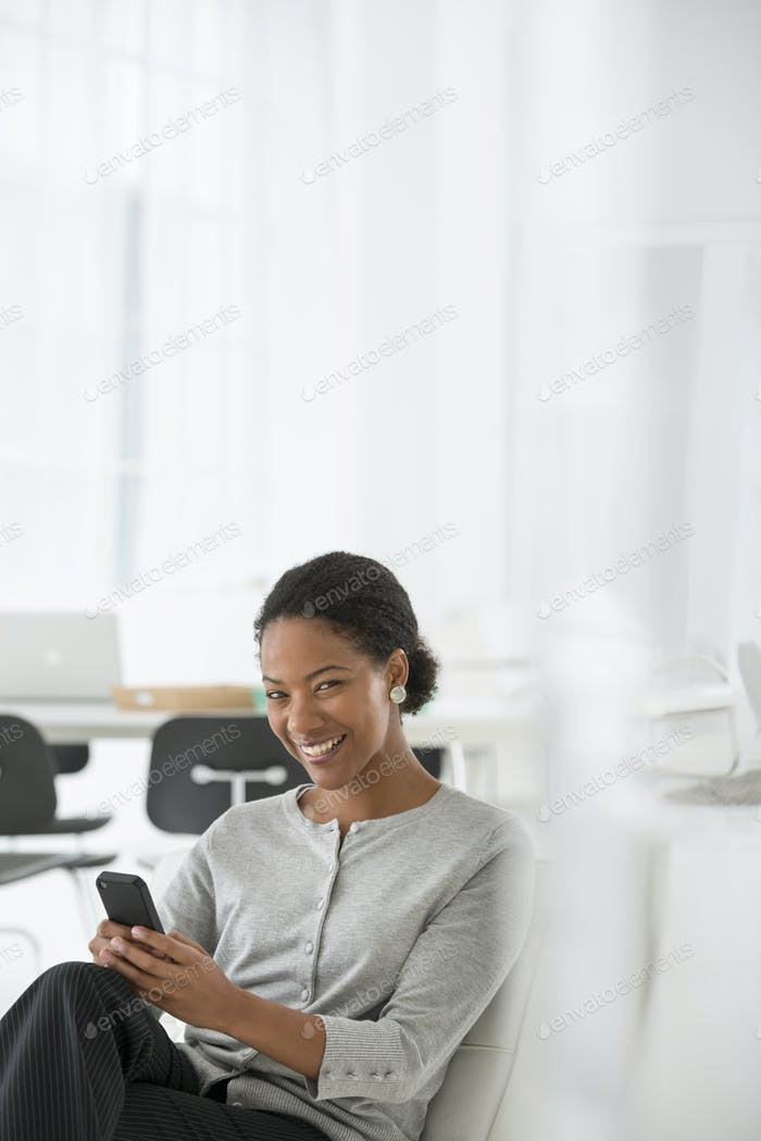 A Business woman in a comfortable office chair, checking her smart phone for messages.