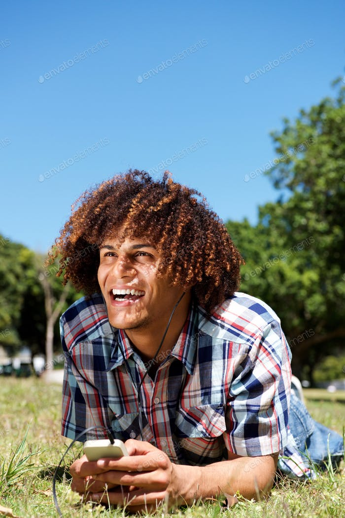 happy young man laughing with cellphone and earphones in park