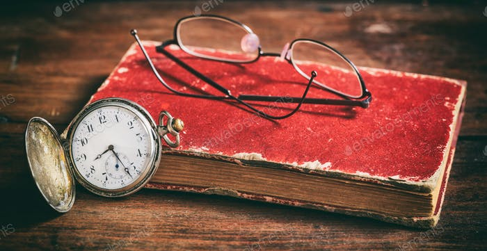Pocket watch and eye glasses on an old book