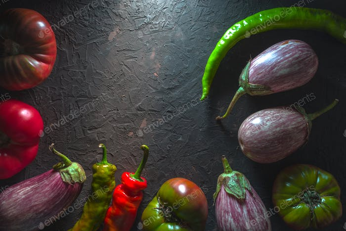 Half-frame of multi-colored tomatoes, aubergine and chili on a gray table