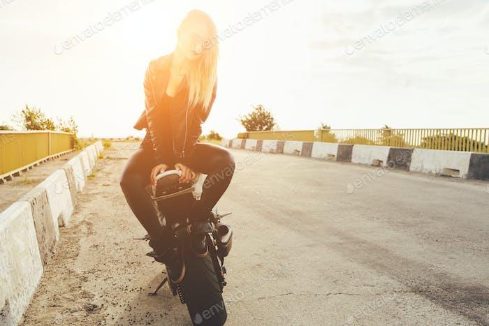 Biker-Mädchen in einer Lederkleidung auf einem Motorrad