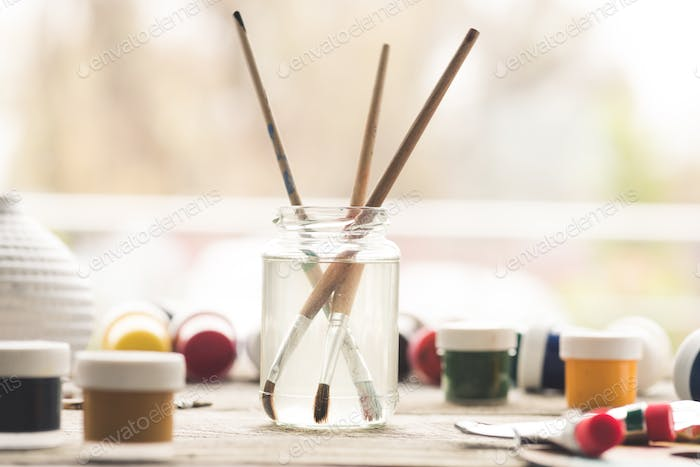 Paint brushes in a solvent and scattered containers with poster paints