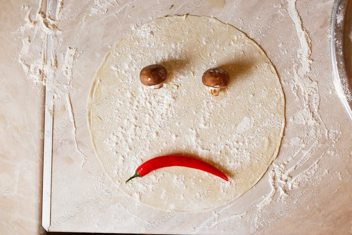 Dough basis for pizza in the shape of sad face