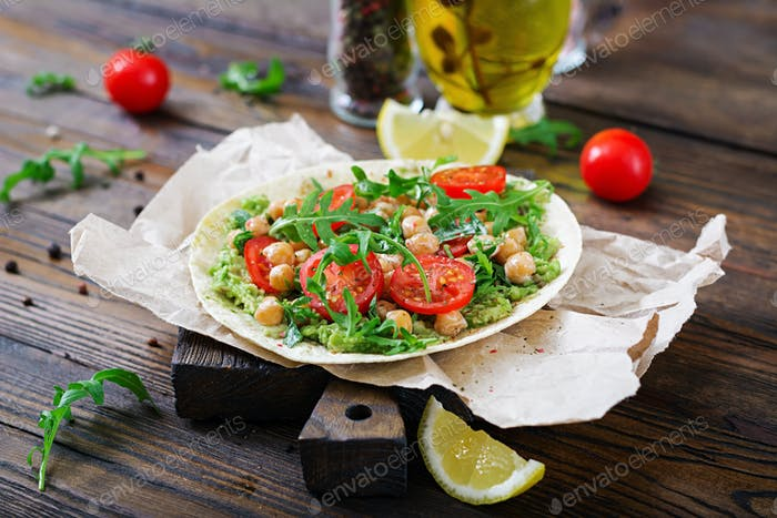 Vegan tacos with guacamole, chickpeas, tomatoes and arugula. Healthy food. Useful breakfast