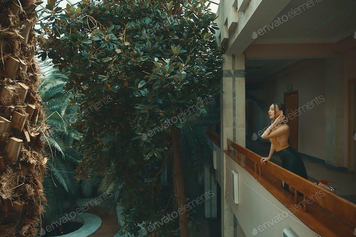 Hübsche junge Frau steht auf Hotelbalkon und schaut