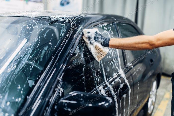 Carwash service, worker soaps glasses