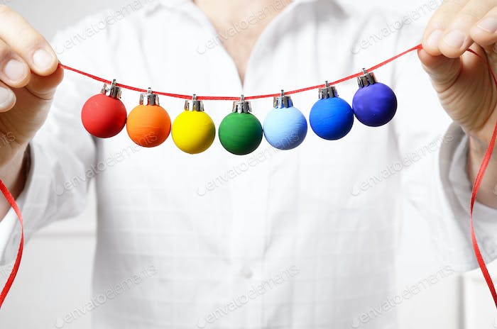 Middle aged caucasian male model in unbuttoned shirt hold painted Christmas balls. Space for text