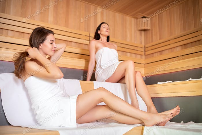 Two beautiful females sitting and relaxing in sauna