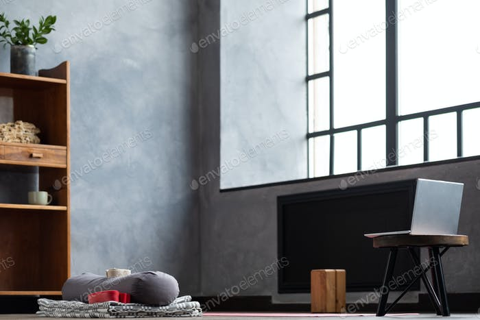 Yogamatte im leeren Loft-Raum Innenraum mit Laptop.