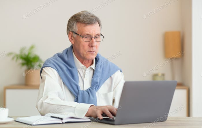 Серьезный старший джентльмен в ноутбук компьютер сидит в современном офисе