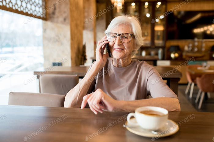 Positive senior entrepreneur talking by phone