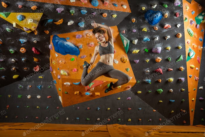 Pretty young woman jumping in climbing gym