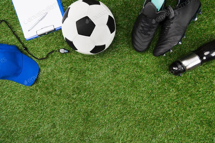 top view of clipboard with soccer ball and boots on grass