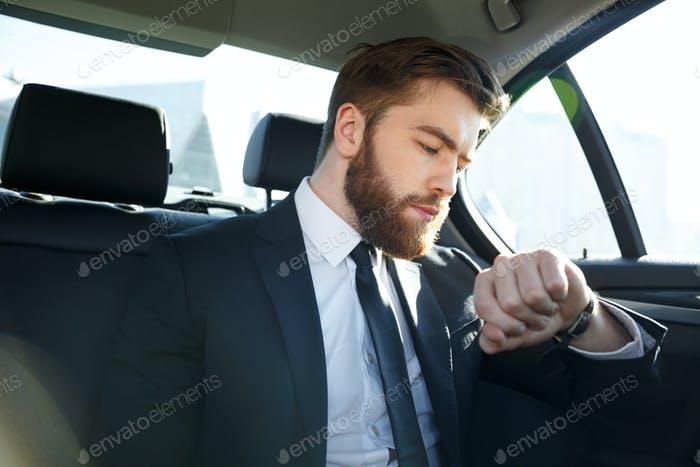Confident young businessman looking at his watch