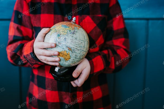 A little boy is holding a globe