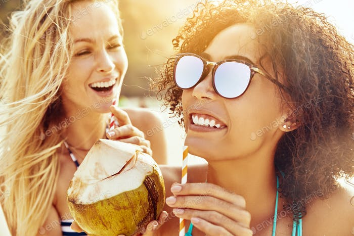 Laughing female friends sipping from coconuts on a sandy beach