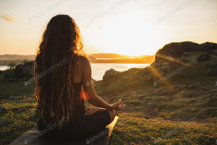 Woman meditating yoga alone at sunrise mountains. View from behind. Harmony with nature.