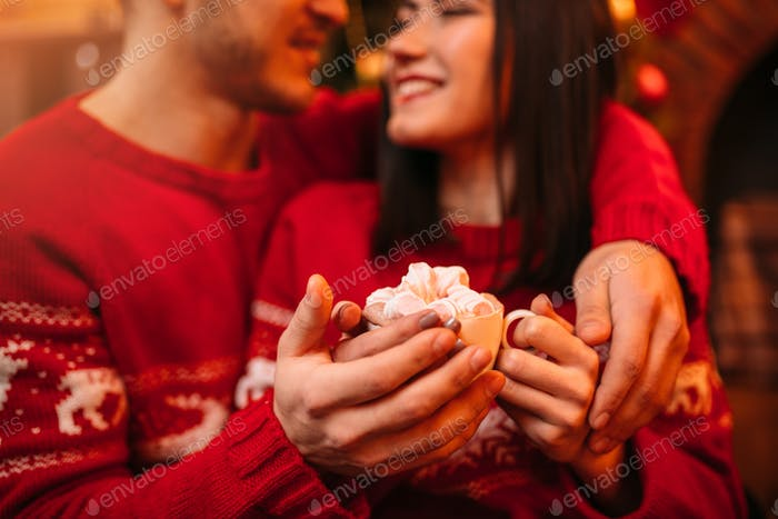 Love couple warm hands on a Cup of coffee, xmas