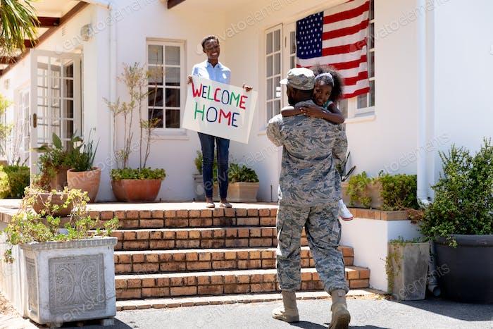 Afroamerikaner Frau und ihre Tochter stehen willkommen einen afroamerikanischen Soldaten